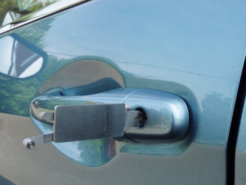 cyan colored car door lock getting picked open by a locksmith