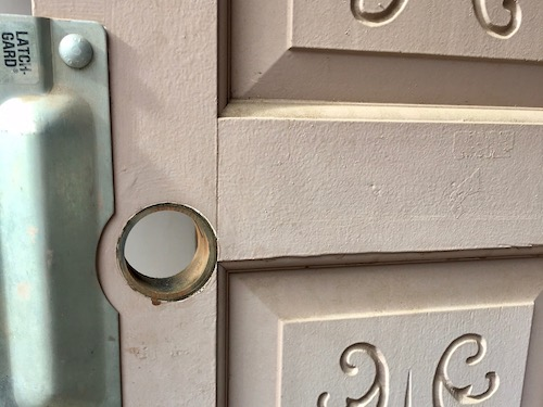 silver latch protector mounted on a wooden residential door