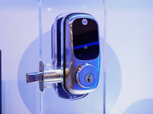 A silver Yale smart lock with key override mounted for display.